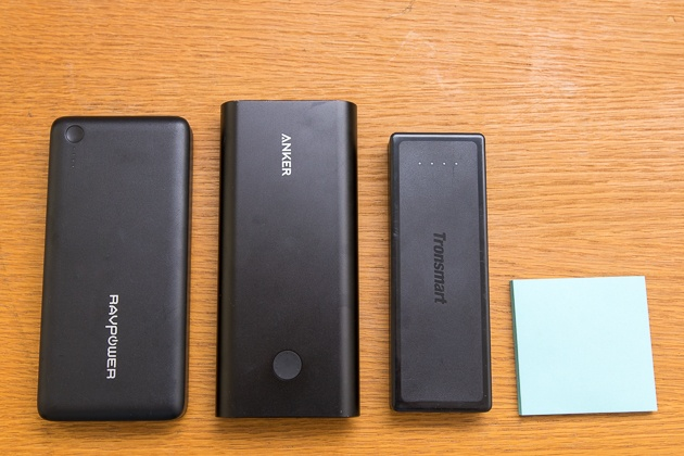 Our three picks for usb-c battery pack sitting on a wooden tabletop next to a post it note for scale.